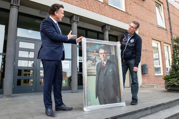Gemeentesecretaris René Wiersema (l) overhandigt Marcel Fehling het schilderij van zijn opa. Het aan de gemeente geschonken schilderij bleek verdwenen toen Fehling het wilde komen bekijken. Na een artikel in de krant dook het weer op.