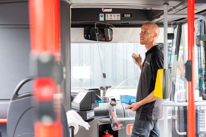Een medewerker van vervoersbedrijf Arriva installeert in een bus een kuchscherm bij de bestuurdersplaats.