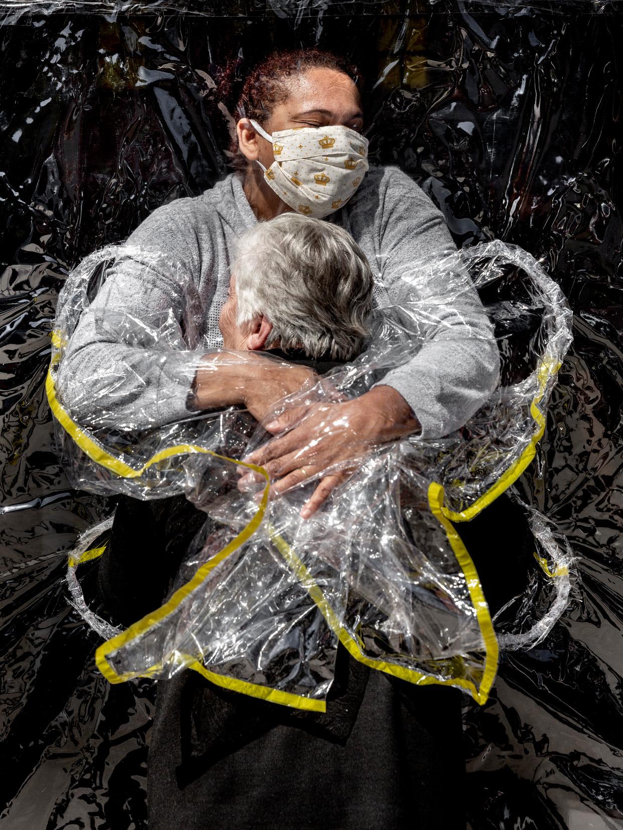 Na vijf maanden zonder aanrakingen krijgt de 85-jarige Braziliaanse Rosa Luzia Lunardi voor het eerst een omhelzing van haar verpleegster. Coronaproof, uiteraard. (Mads Nissen) Beeld Mads Nissen/ Politiken/ Panos Pi