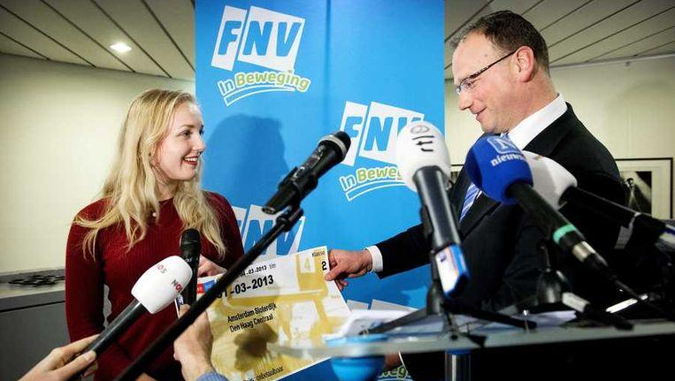 FNV-voorzitter Ton Heerts krijgt een treinkaartje naar Den Haag aangeboden tijdens een persconferentie waarin Heerts de inzet van FNV presenteert voor het overleg met werkgevers en het kabinet over de Sociale Agenda. Beeld anp