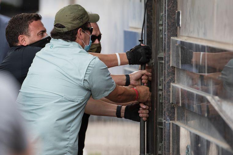 Amerikaanse agenten forceren de achterdeur van het Chinese consulaat in de Amerikaanse stad Houston. Beeld AP