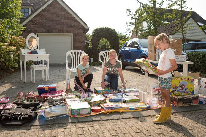 Myrthe (12 jaar) en Lieke (10 jaar met bril) verkopen hun spulletjes. Hidde van Loon bekijkt een spel die hij misschien wil kopen.