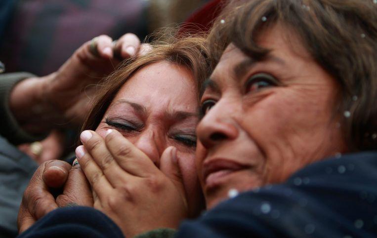 Roxana Gomez, de dochter van mijnwerker Mario Gomez, wordt getroost door Maria, de zus van Dario Segovia. Beeld UNKNOWN
