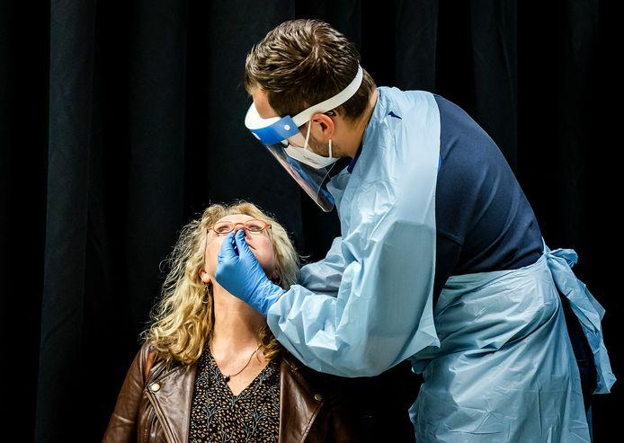 Een vrouw laat zich testen op het coronavirus. Maandag werden in Twente 76 positief getest op het coronavirus.