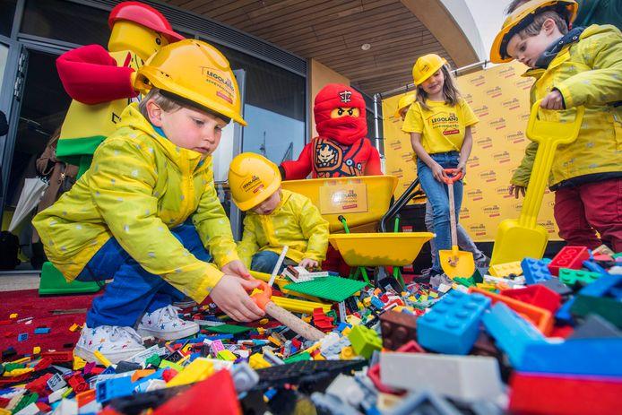 De drie Scheveningse broers Boris (4), Elvis (bijna 3) en Nelson (5) helpen met het scheppen van de eerste 30.000 LEGO-steentjes die arriveren bij Legoland Scheveningen.