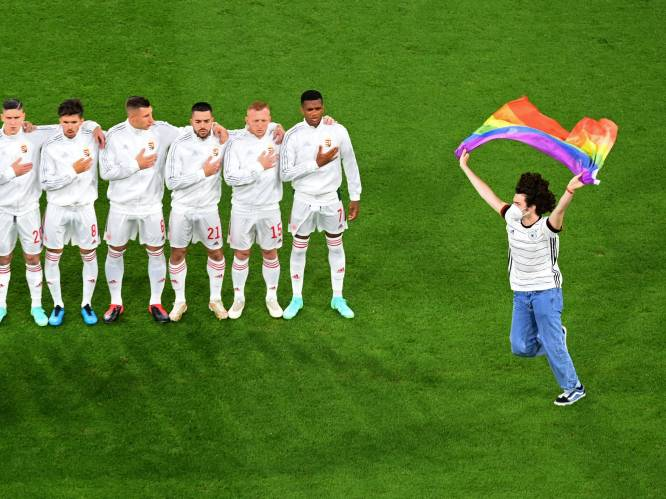 Demonstrant met regenboogvlag op het veld bij Hongaars volkslied