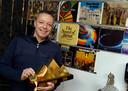 Dick Jasper met de trofee die hij won bij het WK driebanden in Egytpe in 2018 bij de platenhoezen van zijn favoriete muziekalbums in zijn eigen biljartzaal.
