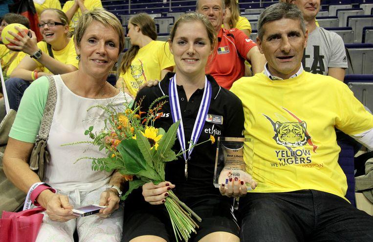 Valérie Courtois, zus van, poseert tussen haar ouders. Beeld BELGA