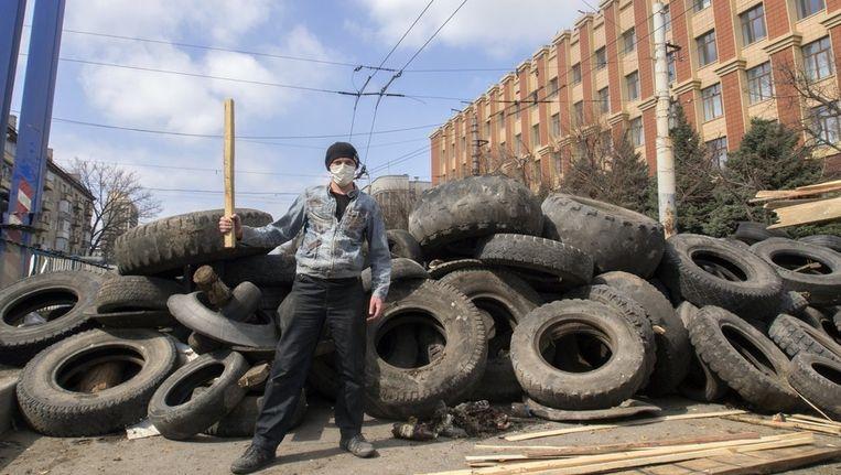 Een pro-Russische betoger voor de barricades in Loehansk. Beeld AP