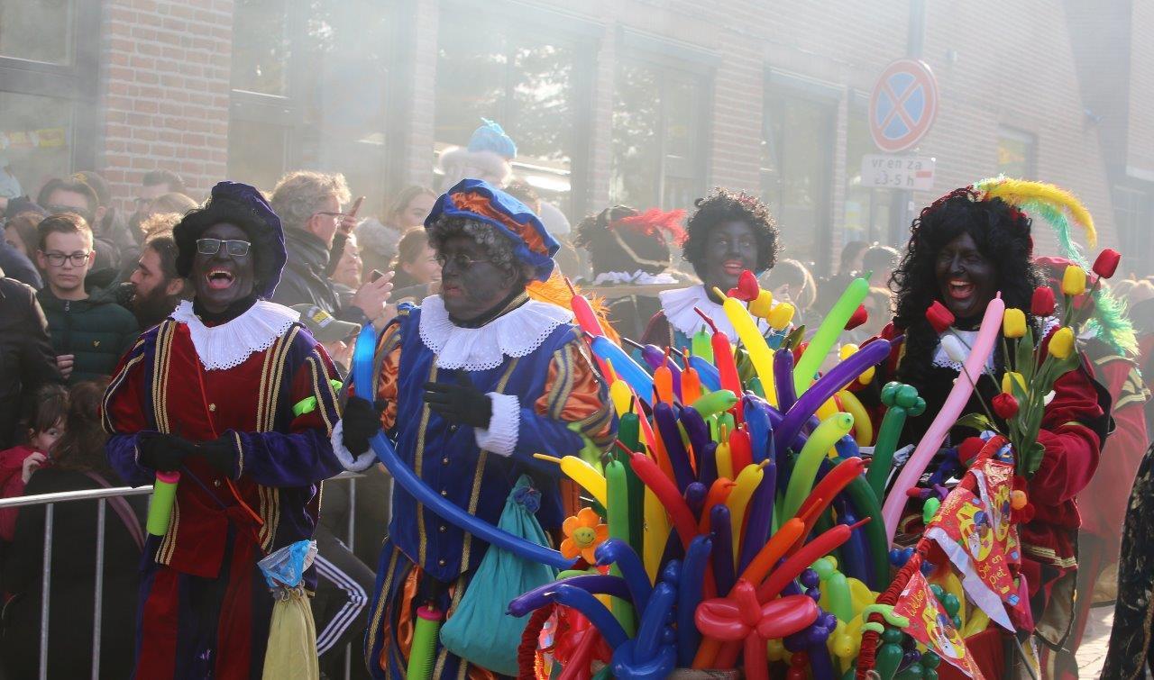 Pieten delen ballonnen, bloemen en pepernoten uit aan kinderen langs de route in de binnenstad.