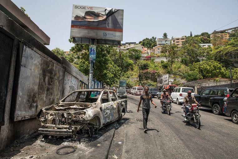 Een uitgebrande auto nabij het politiebureau in Perionville in Haïti waar de verdachten van de liquidatie van president Moïse vastzitten. Beeld AFP