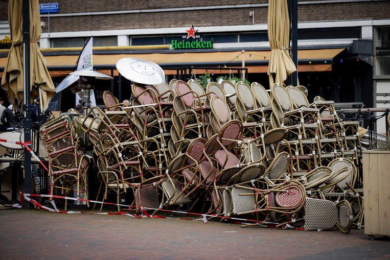 Stoelen en tafels van een terras staan nog opgestapeld op de Binnenrotte in Rotterdam.  Beeld ANP