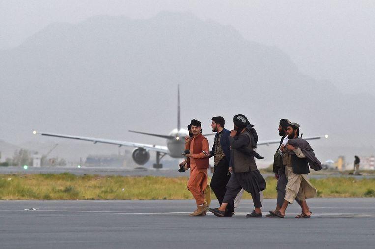 Talibanstrijders op de luchthaven in Kabul.  Beeld AFP