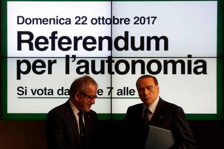 Roberto Maroni, gouverneur van Lombardije, poseert met de Italiaanse oud-premier Silvio Berlusconi voor een poster voor het referendum voor meer autonomie. Beeld AP