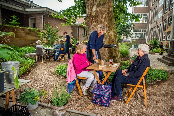 Tuinman Anna Veenstra serveert bij de grote plataan gerechtjes van kok Ceciel Landsaat.