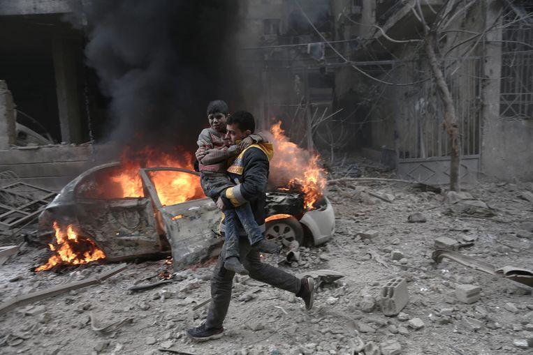 Een Syrische hulpverlener met een gewond kind in Hamouria, Oost-Ghouta begin dit jaar.