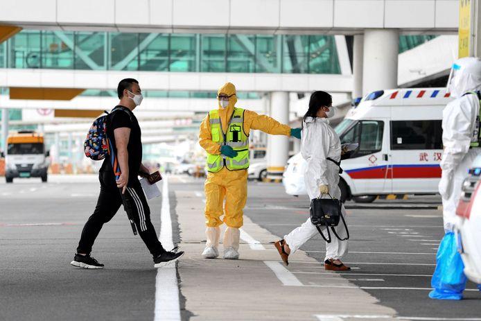 De 60 reizigers aan boord van de T'way-vlucht werden naar het luchthavengebouw begeleid, opnieuw door een medewerker in speciaal pak.