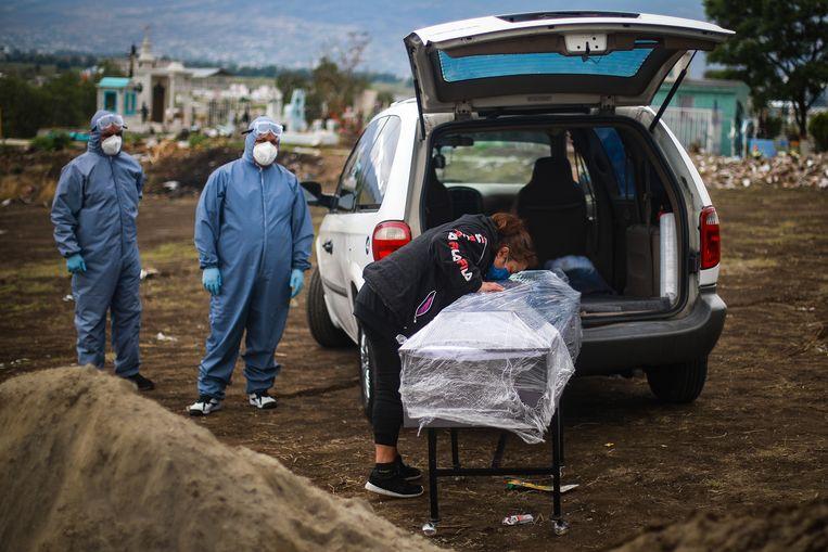 Een vrouw neemt afscheid van haar overleden familielid onder corona-omstandigheden in Valle de Chalco, Mexico.  Beeld Getty Images