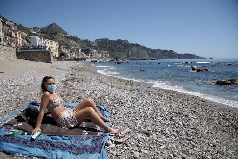Een vrouw met mondkapje op het strand van Sicilië.  Beeld REUTERS
