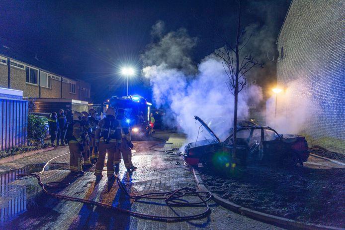 Het bluswerk is gedaan, de wolken stoom hangen er nog. Er bleef van deze auto in Apeldoorn weinig over nadat die in brand was gevlogen.