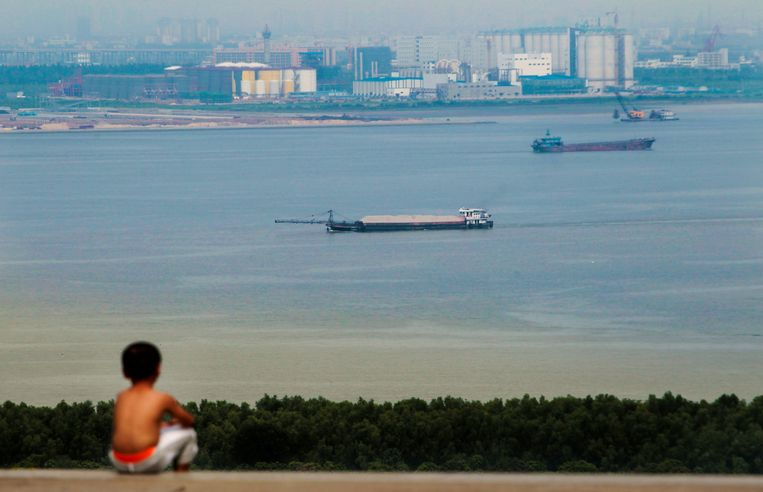 A boy looks at cargo ships passing along the Pearl River in Guangzhou, Guangdong province. Beeld REUTERS