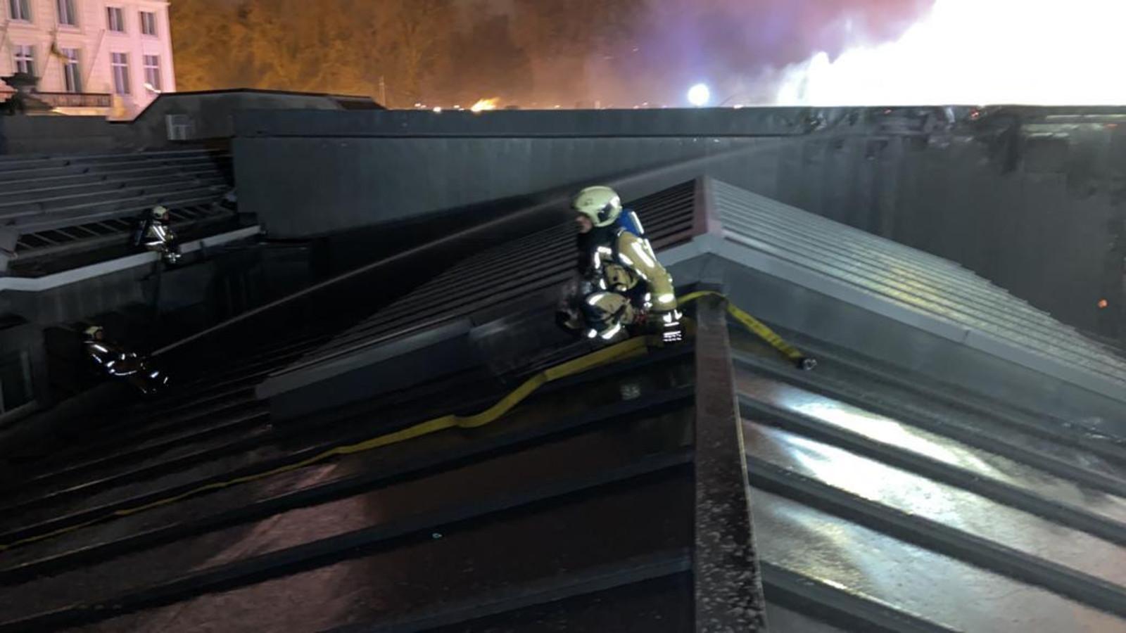Brandweermannen blussen op het dak.