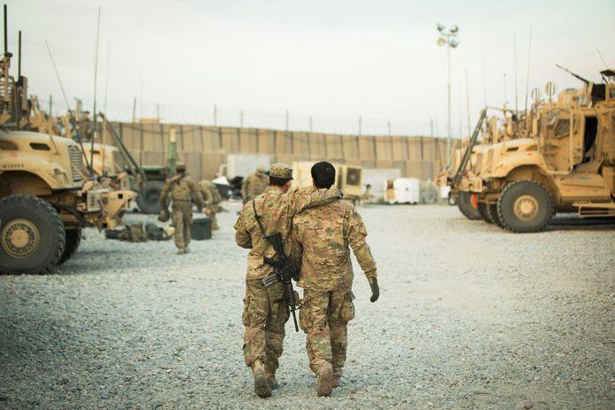 Foto van december 2014. Een Amerikaanse soldaat loopt weg met een arm geslagen om een Afghaanse tolk.