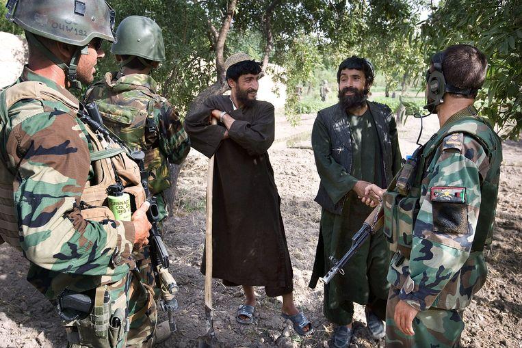 Nederlandse militairen, bijgestaan door twee Afghaanse tolken in gesprek met Afghaanse boeren in de Balouzi Vallei in 2008.  Beeld Guus Dubbelman / de Volkskrant