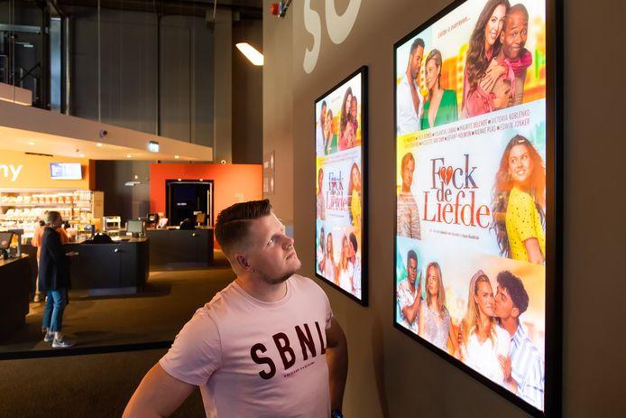 Evert van de Grift, producent van bios-topfilm F*ck de liefde, naast de posters in Kinepolis Breda. Ook op de website van de bioscoop in Breepark werden poster en trailer enorm vaak bekeken.