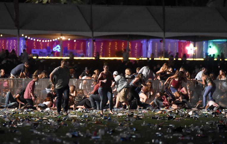 Mensen vluchten weg van het muziekfestival in Las Vegas, waar een schietpartij aan zeker twintig mensen het leven kostte. Beeld AFP