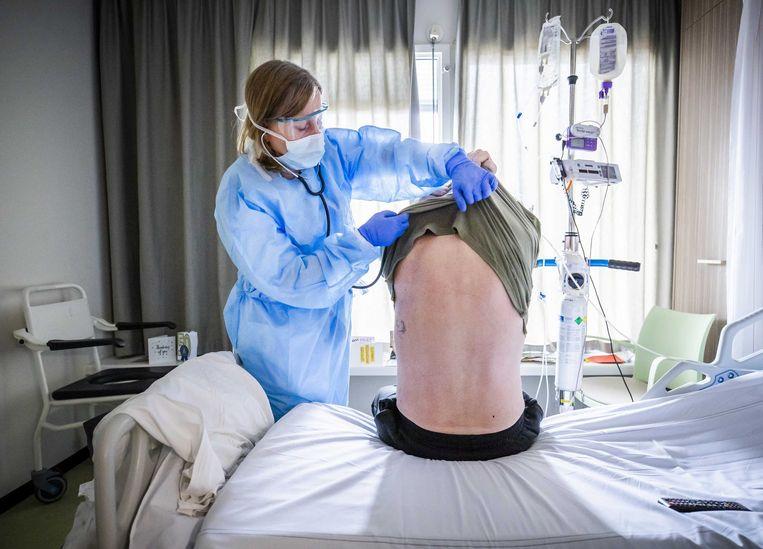 Een behandelend arts in het HMC Westeinde luistert naar de longen van een coronapatiënt die herstellende is van ic-opname. Beeld ANP
