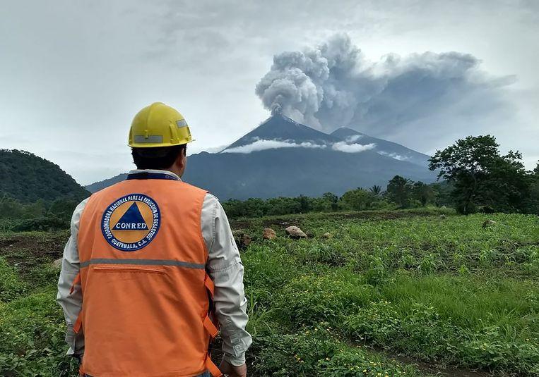 Een lid van de civiele bescherming van Guatemala kijkt vanaf een afstand naar de Fuego-vulkaan die uitbarstte in Guatemala. Beeld AFP