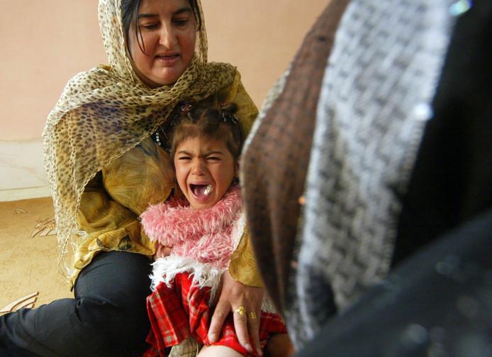 Foto ter illustratie. Een jong Koerdisch meisje (midden) tijdens haar besnijdenis in 2009.