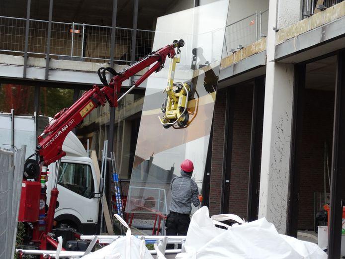 Eén voor één zijn de panelen van het gigantische glaskunstwerk van het stadskantoor vorige week uit het gebouw getild.