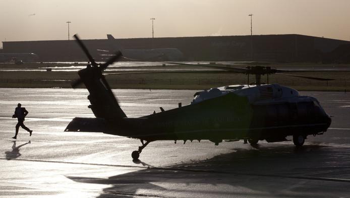 Een Amerikaanse veiligheidsagent loopt langs de Marine One helikopter die klaar staat voor de aankomst van president Barack Obama op Schiphol.