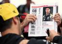 Daniel Ricciardo zet een krabbel op een tijdschrift voor een fan.