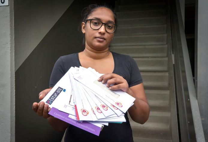 Nivana Rampersad met de post die zij op de trap voor haar huis vond. Tweederde van de stapel heeft ze bezorgd voordat ze bedacht dat het de verantwoordelijkheid van PostNL was. Tussen de brieven de zit o.a. een verkeersboete, maar ook post van DigiD, de huisartenpost en zorgverzekeringen.