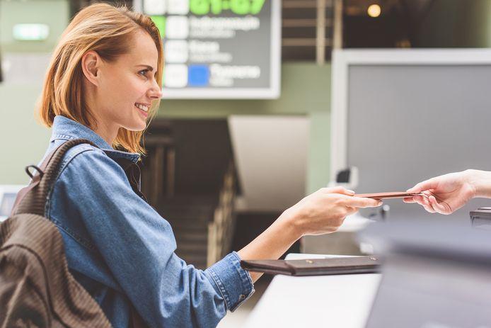 Een vrouw geeft haar reispapieren af bij de incheckbalie. Foto ter illustratie.