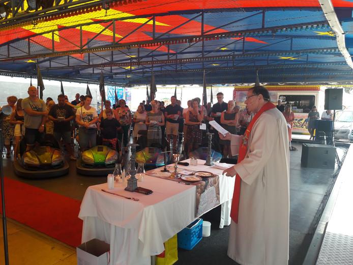 Aalmoezenier Bernhard van Welzenes gaat als pastor voor in de kermismis in de botsautotent.