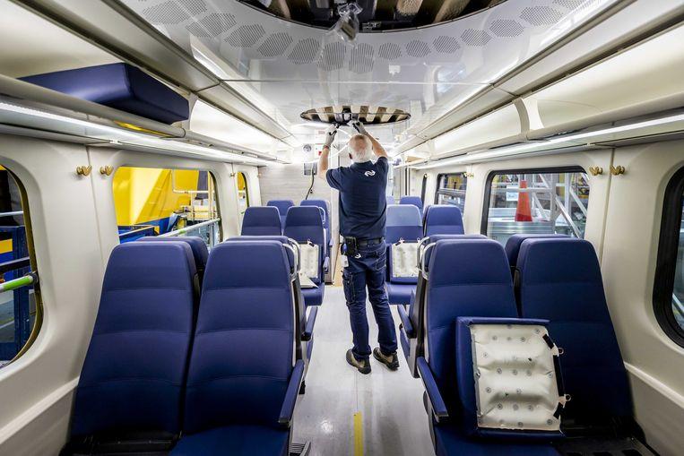 Personeel van NS installeert de nieuwe plafondverlichting in een Virm 2-treinstel. Beeld ANP