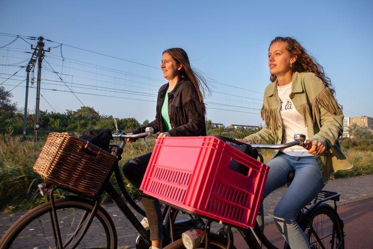 Estelle (links) en Britt fietsen naar school. Normaal doen ze daar 5 minuten over, maar nu moeten ze een heel eind omfietsen omdat de spoorwegovergang is gesloten vanwege alle extra treinen die naar Zandvoort rijden. Beeld Pauline Niks