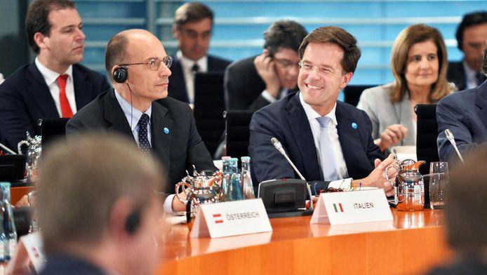 Premier Rutte tijdens de top in Berlijn. Achter hem minister Asscher (Sociale Zaken).