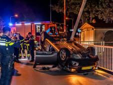 Auto slaat over de kop na botsing tegen brugpeiler in Tilburg