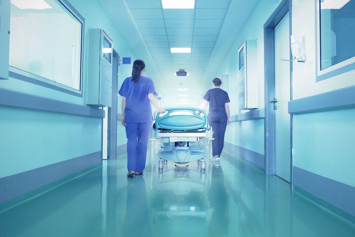 Verpleegsters met een ziekenhuisbed in een gang.