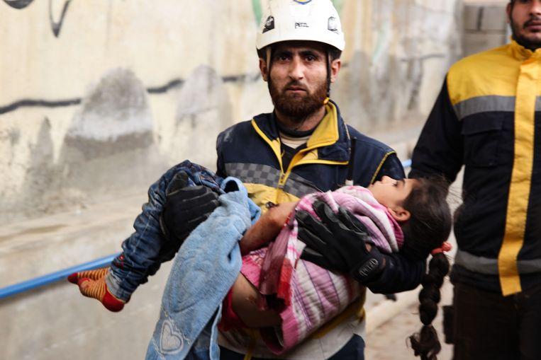 Een reddingswerker draagt een gewond meisje in Idlib, Syrië.