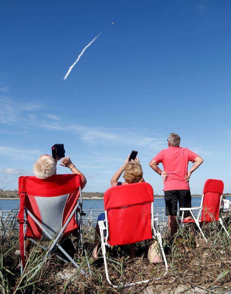 Toeschouwers bekijken de lancering van de Falcon Heavy. Beeld REUTERS