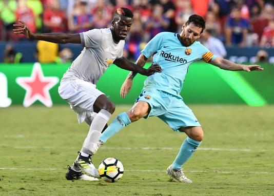 Lionel Messi in duel met Paul Pogba van Manchester United.