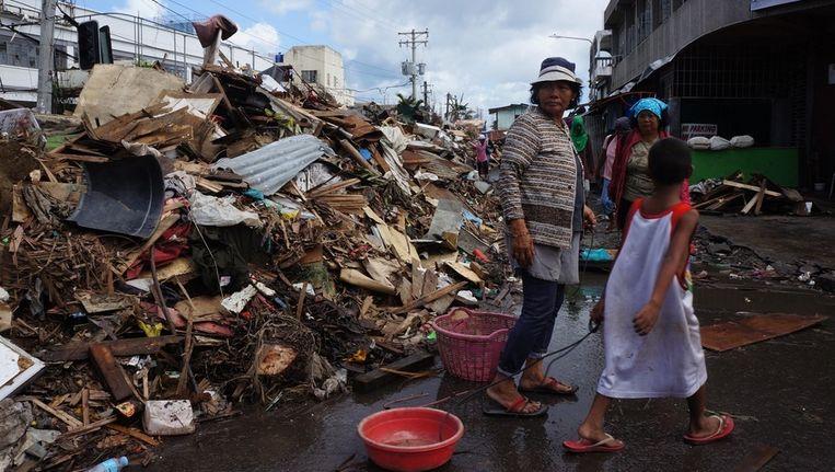 Inwoners van Tacloban lopen langs de puinhopen van tyfoon Haiyan. Beeld GETTY