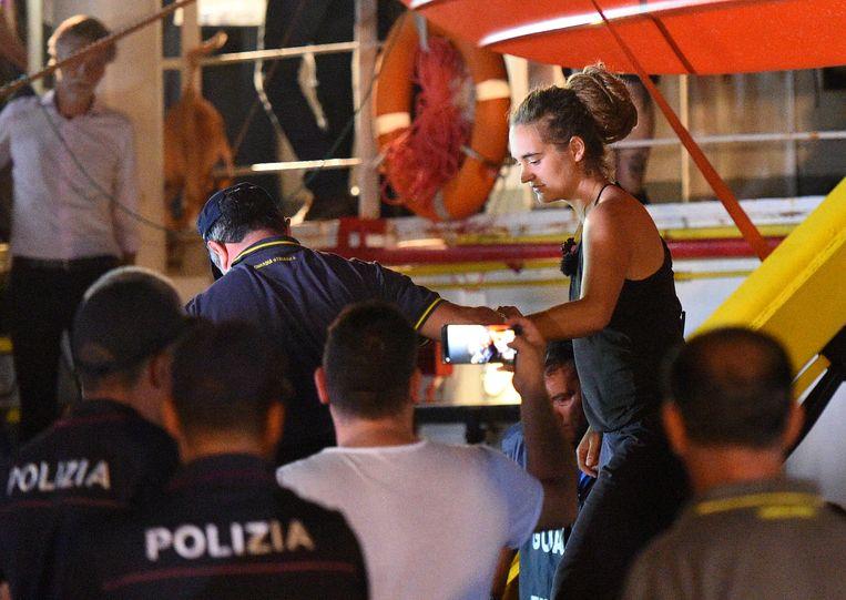Carola Rackete wordt onder politiebegeleiding van haar schip gehaald. Beeld REUTERS