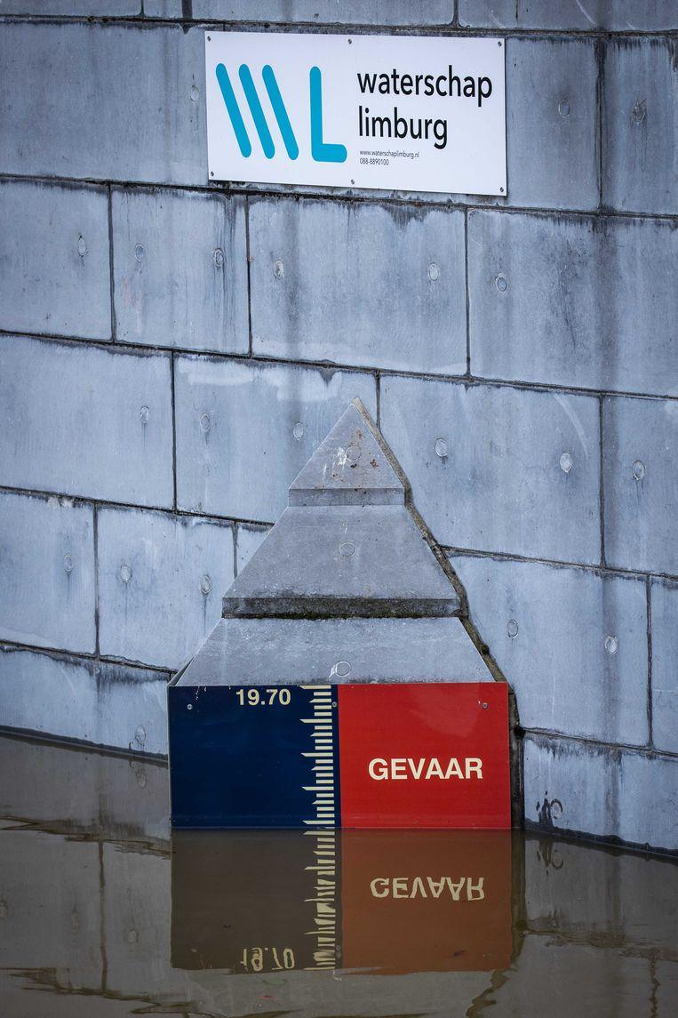 Op een peilstok in de Roer is te zien dat het waterpeil op 'Gevaar' staat. Beeld ANP